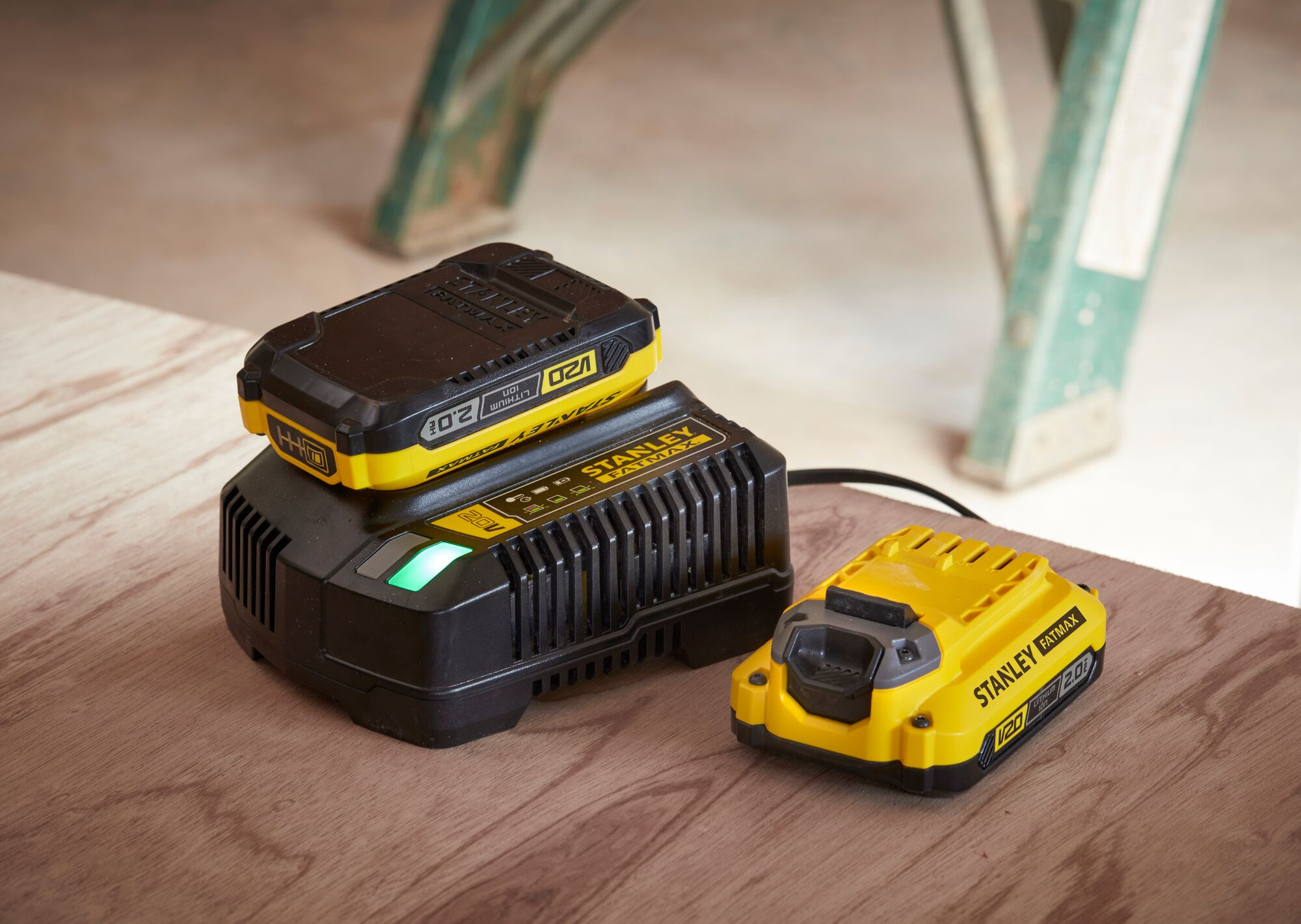 STANLEY FATMAX 20V battery charger with two STANLEY batteries 20V 2.0AH on a wood surface
